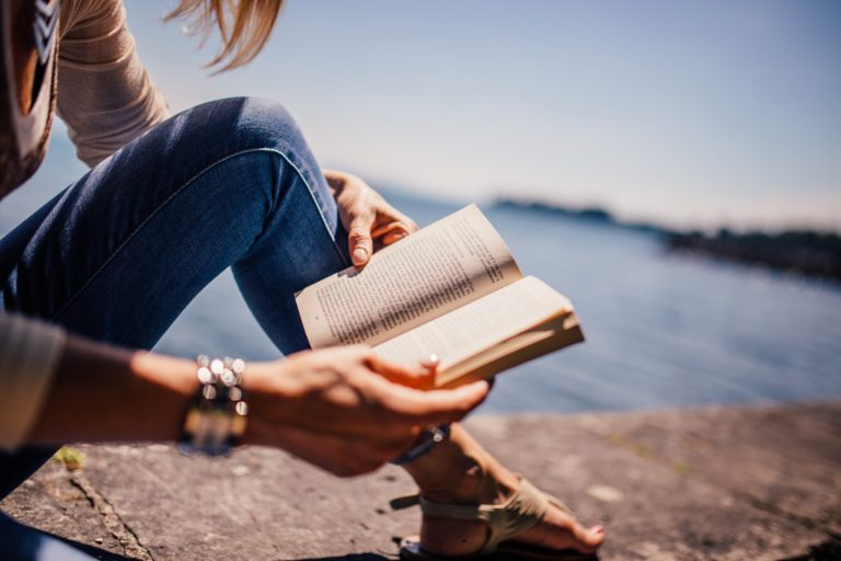 frau beim lesen am see im sommer