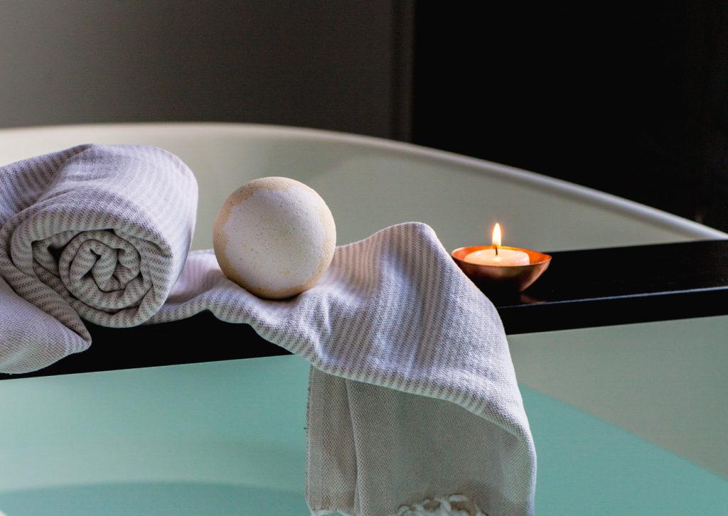 badhandtuch mit kerze auf badewanne