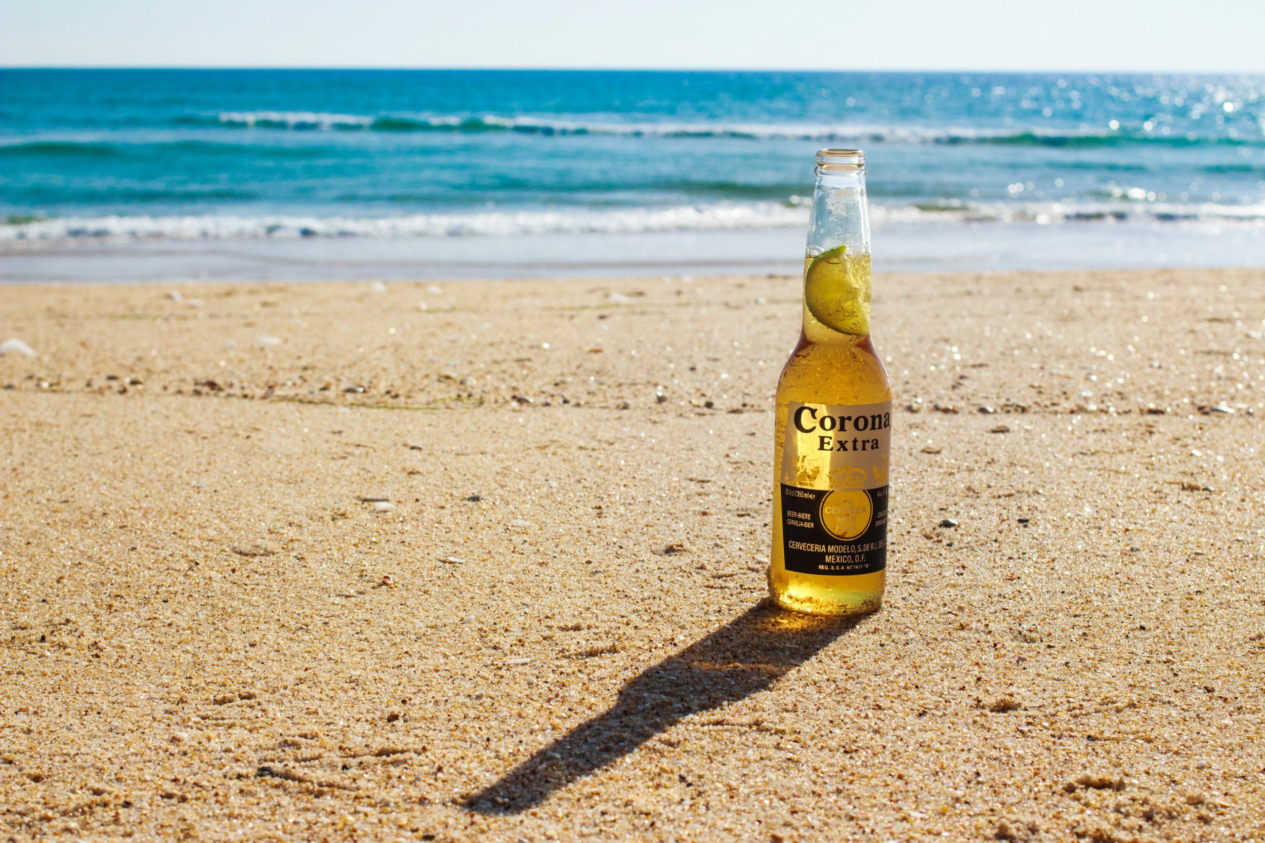 corona bierflasche am strand als zeichen für corona parties